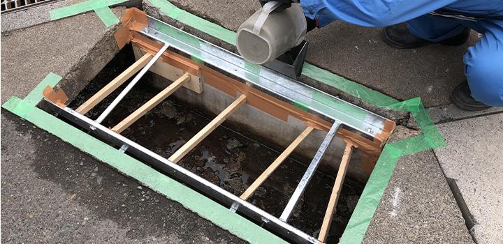 側溝改修の様子 隙間にグラウト材を流し込む